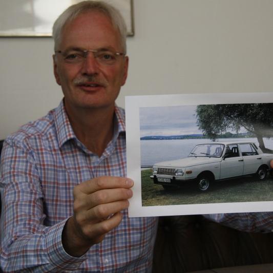 Olaf Damm mit einem Foto des hellblauen Wartburg.